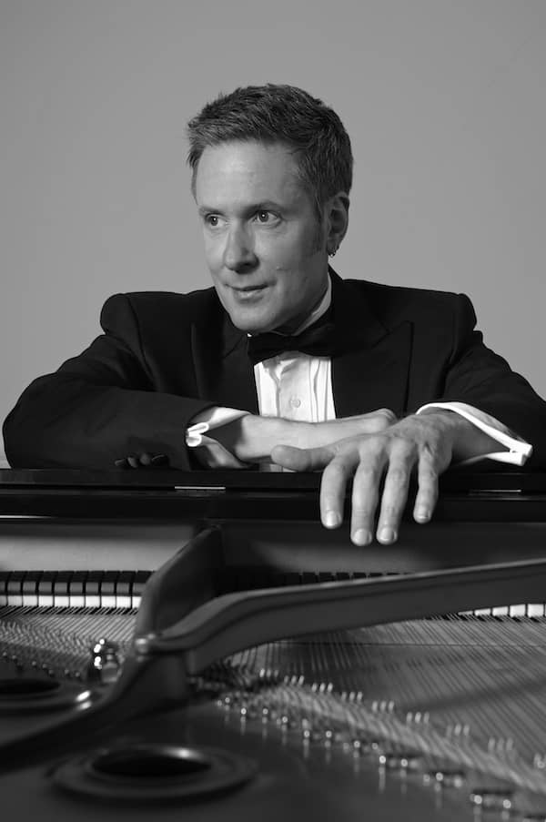 Keith Porter-Snell poses near a piano in a professional headshot.