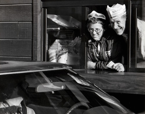 Two people wearing Naugles fast food hats smile outside of a drive-thru window.