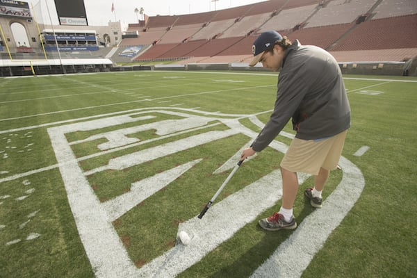 Sean McLaughlin paints the NFL logo on the grass in an empty stadium