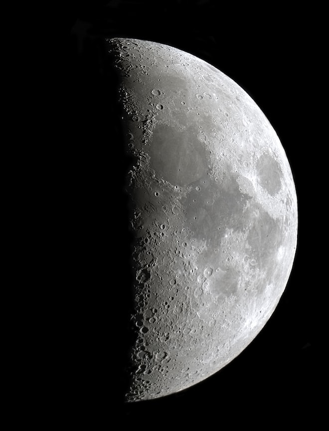 An extreme close up of the moon. Half is in light, half is in darkness.