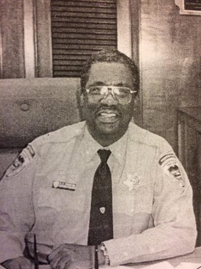 Frank Thompson in a guard uniform at a desk