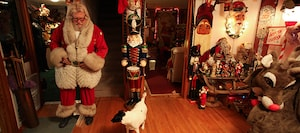A man dressed as Santa is in a room full of Christmas decor.