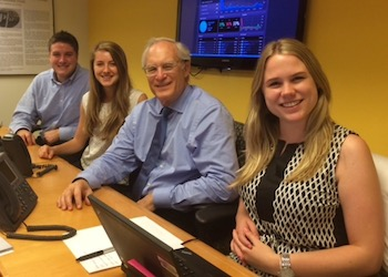 Four interns, Paul and three younger interns, at a conference table.