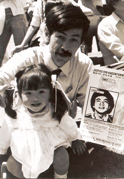 A man with his child hold up a flyer that reads Justice for Vincent Chin.